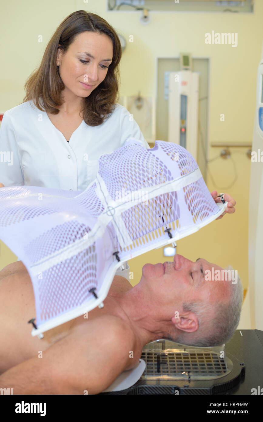 nurse putting mask on patient before radiation therapy - Stock Image