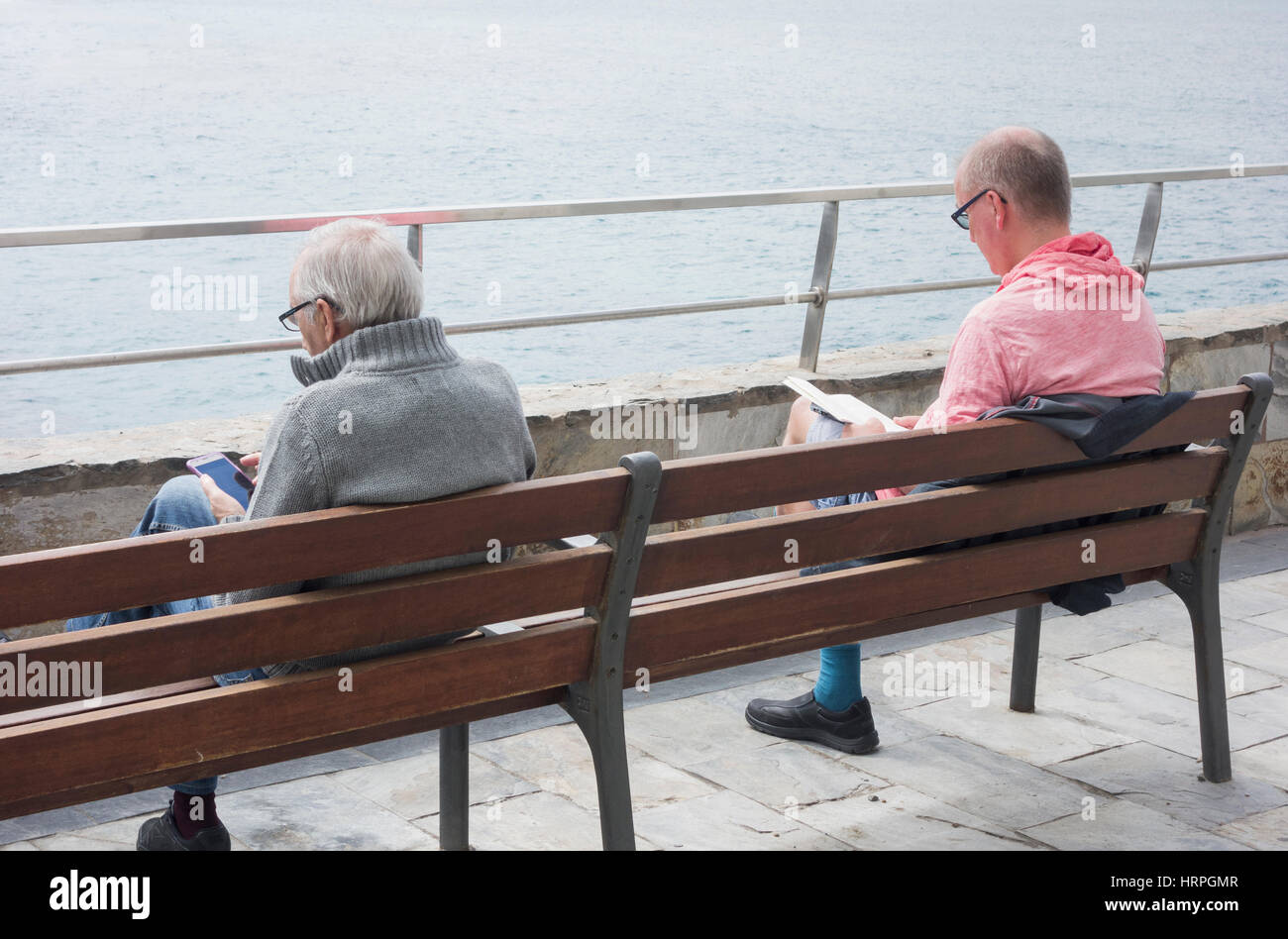Two men reading overlooking the sea. One with paperback book and the other with mobile device. Stock Photo
