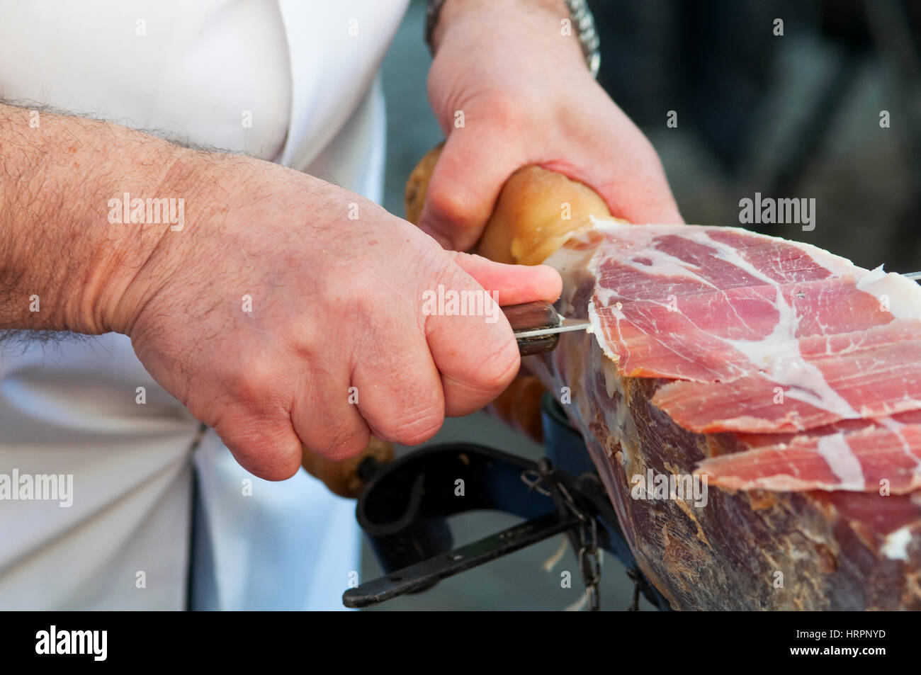 Italy, Umbria, Norcia, Stall Market, Market Stall Trader Carving a Ham - Stock Image