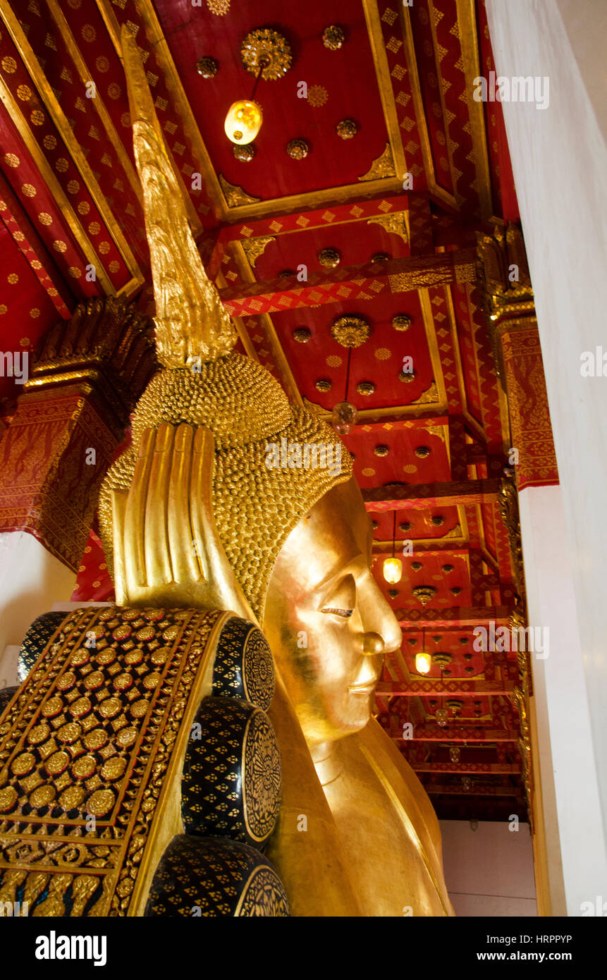 Big golden reclining buddha statue in ubosot or chapel at Wat Pa Mok Worawihan temple for people pray and visit - Stock Image