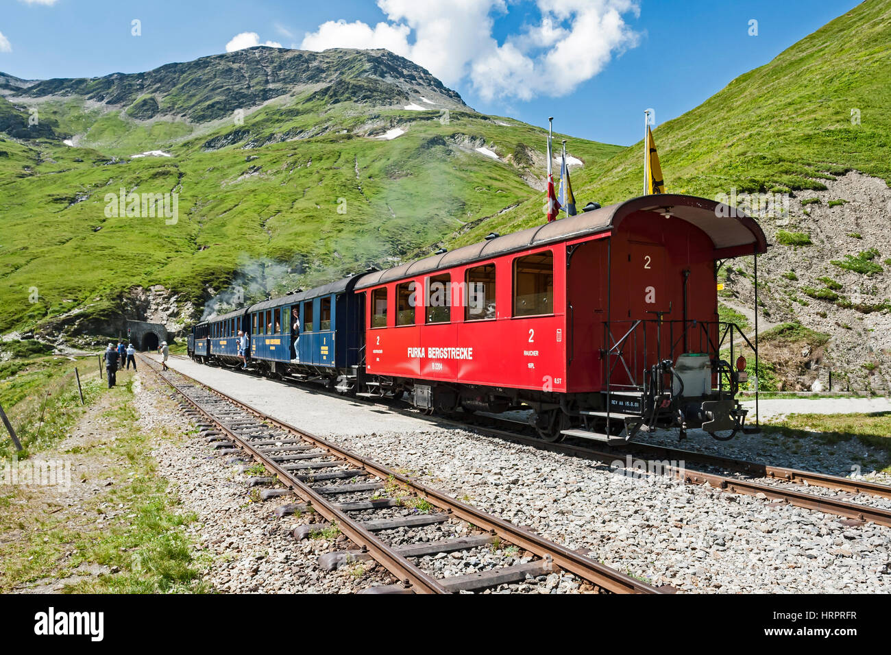 Furka Steam train pausing to take water en route from Realp to Gletch in Switzerland Stock Photo