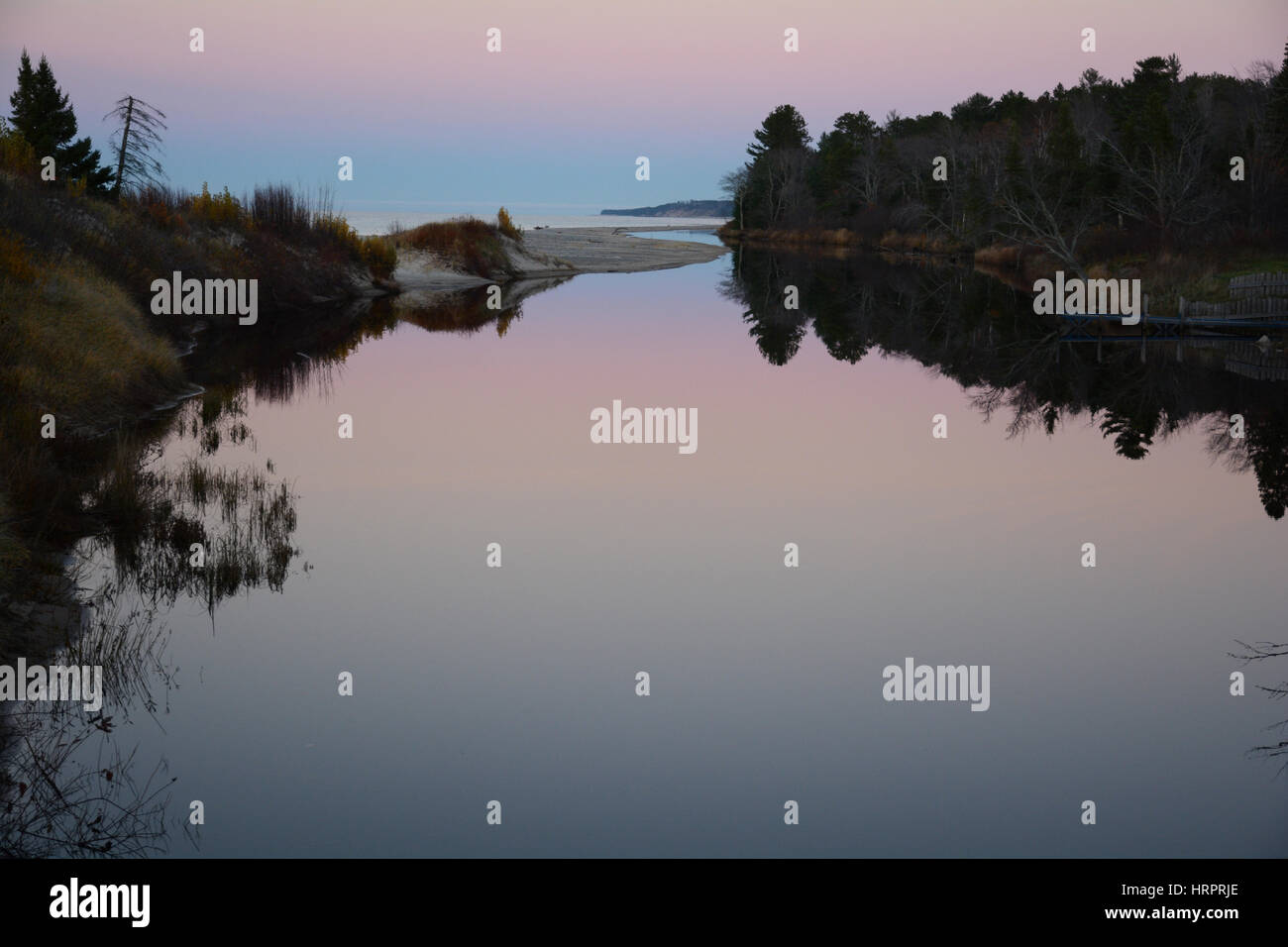 Looking down a very calm river after the sunset with the pink and blue sky and trees reflecting in the water. Stock Photo