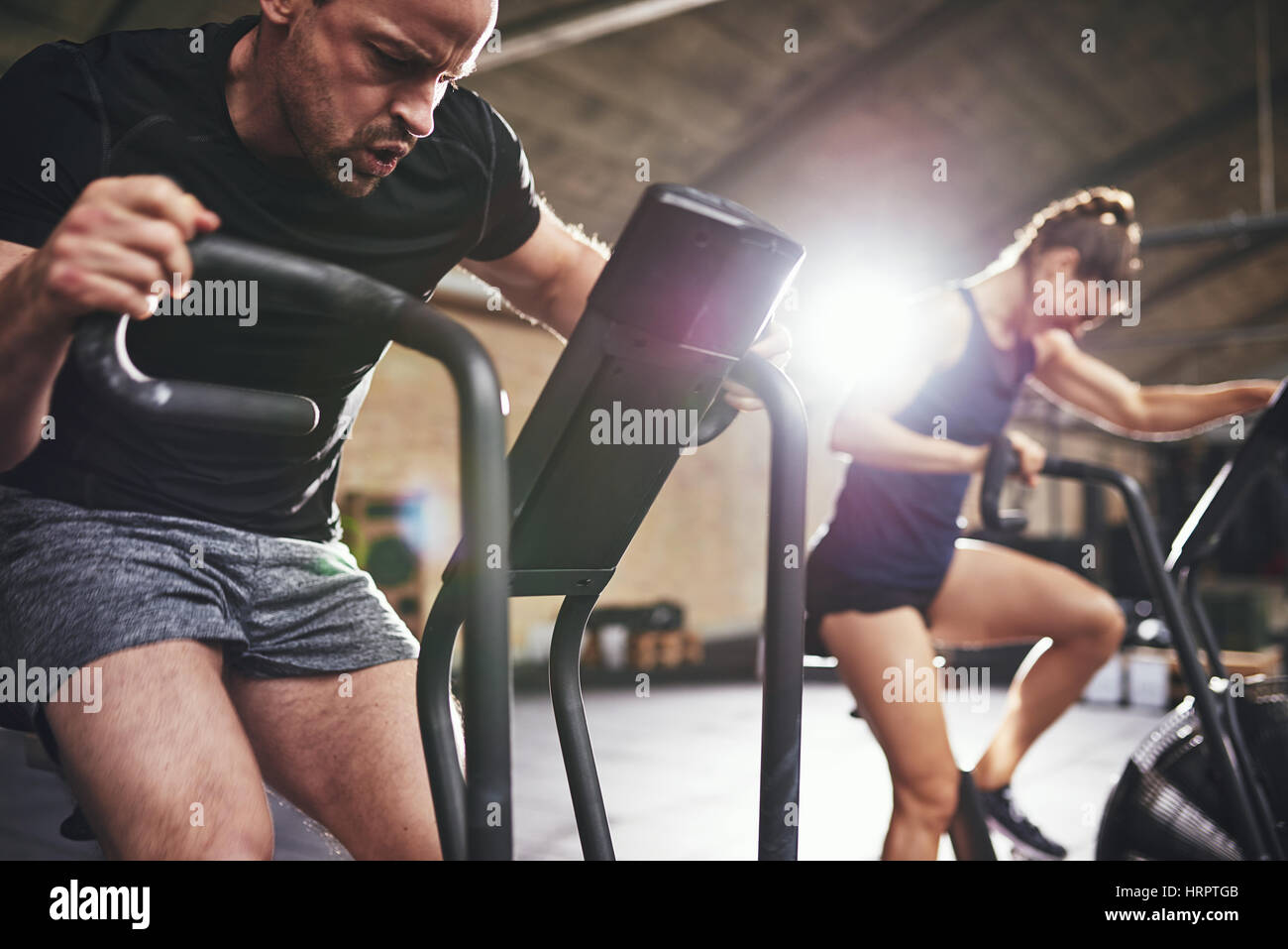 Young man and woman grimacing and riding cycling machines in hard efforts. - Stock Image