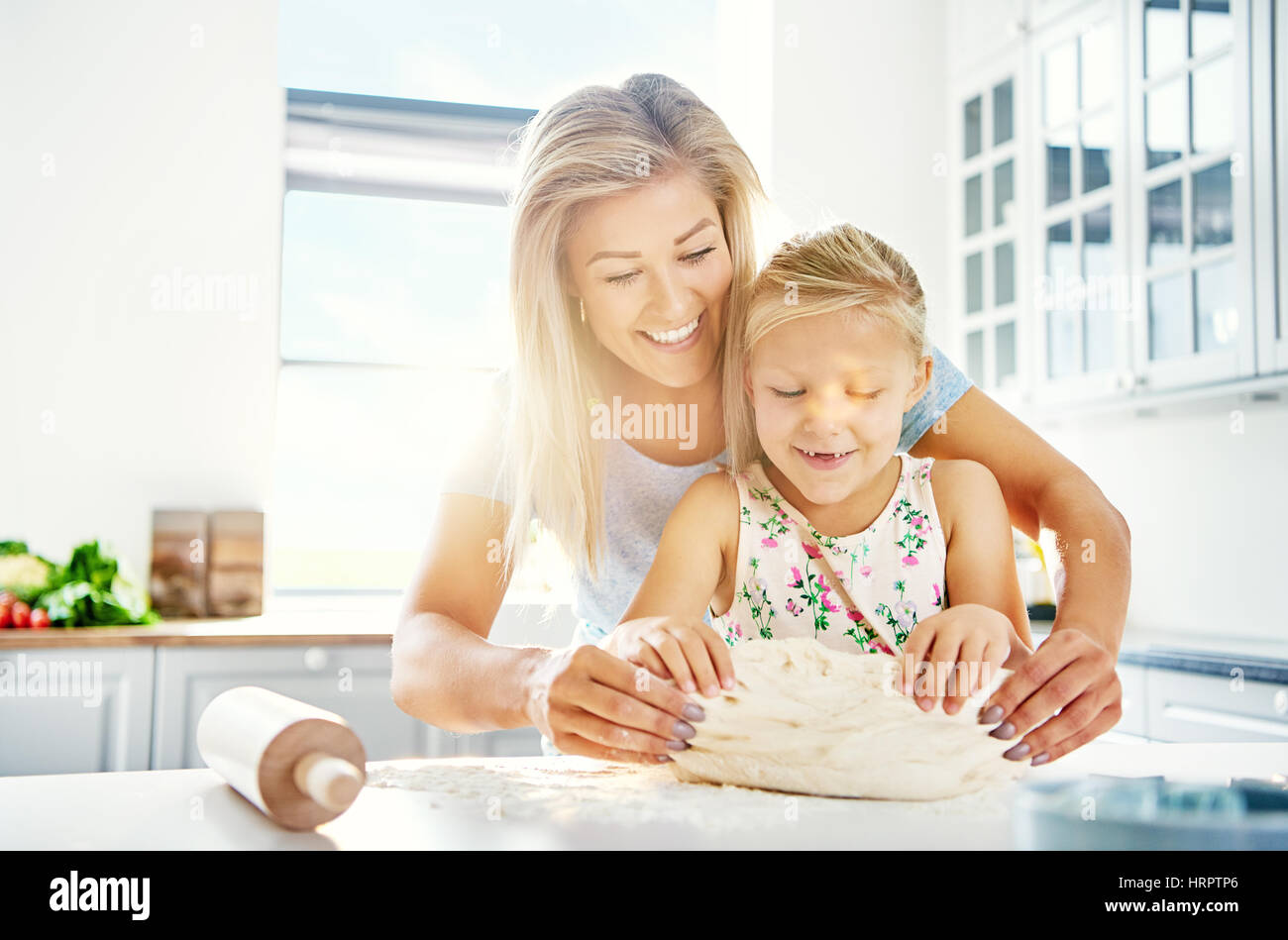 Pretty little girl kneading dough with her mother laughing with joy as she learns to bake, close up view with bright Stock Photo