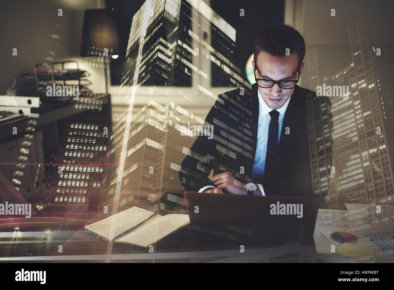 Optimistic businessman working on laptop at office in the night, Working overtime with big city in background - Stock Image