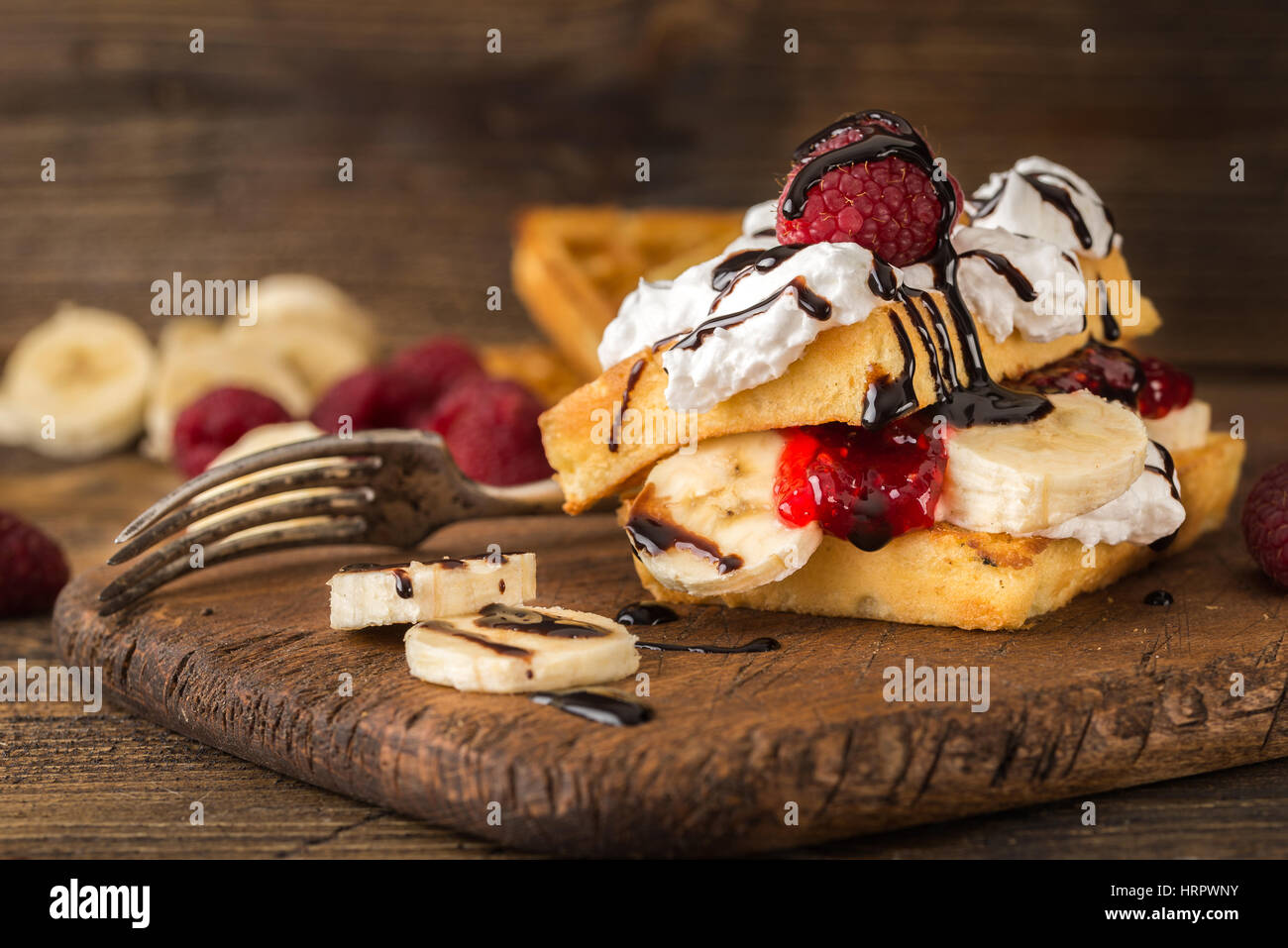 Belgian waffles with raspberries, bananas and double cream on rustic table. - Stock Image