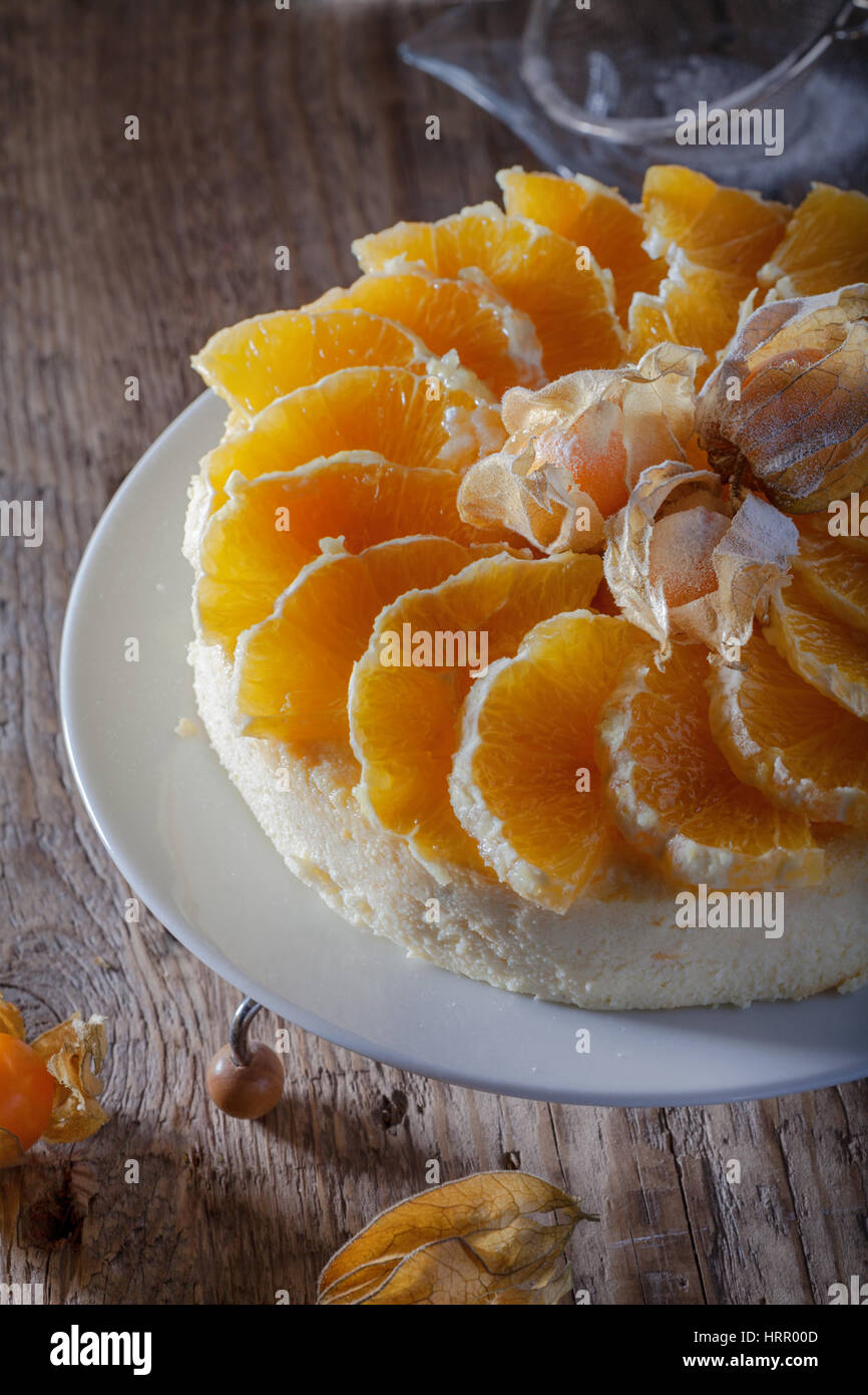 Cheesecake decorated with oranges and physalis on a - Stock Image