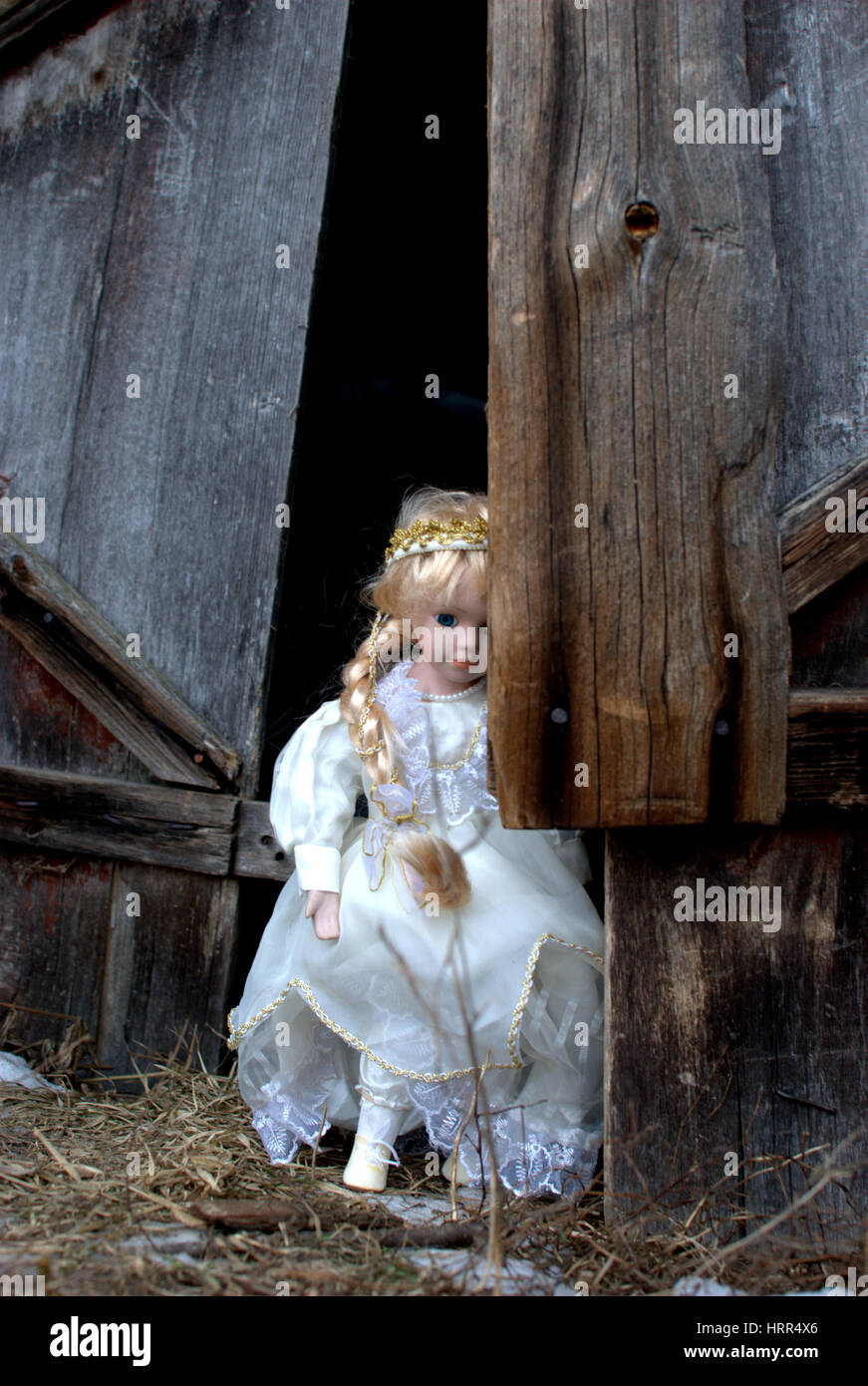 An old doll decided to travel herself arround old farmstead - Stock Image