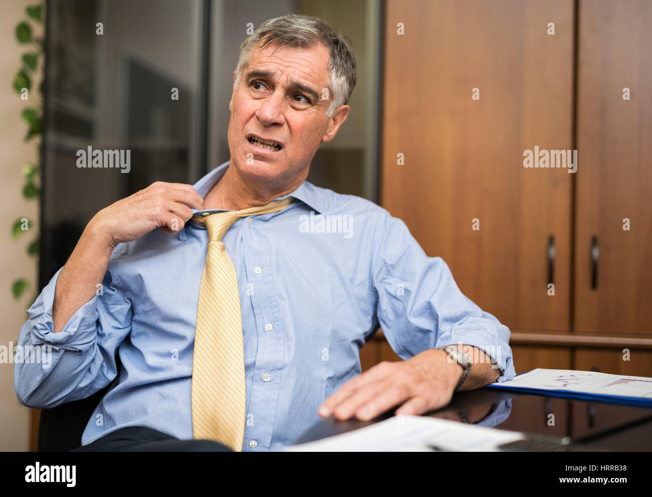 Businessman sweating in his office - Stock Image