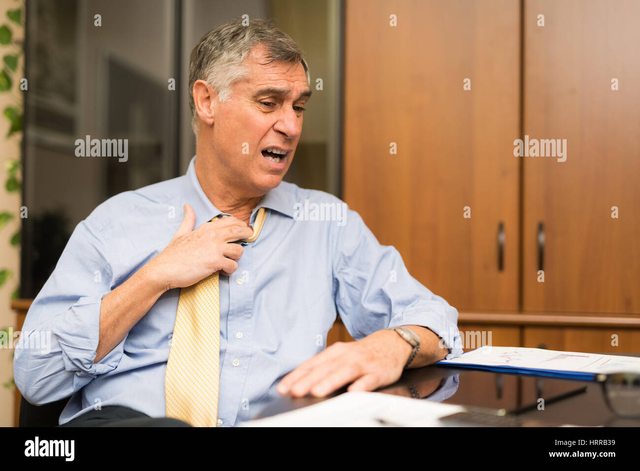 Business man sweating in his office - Stock Image