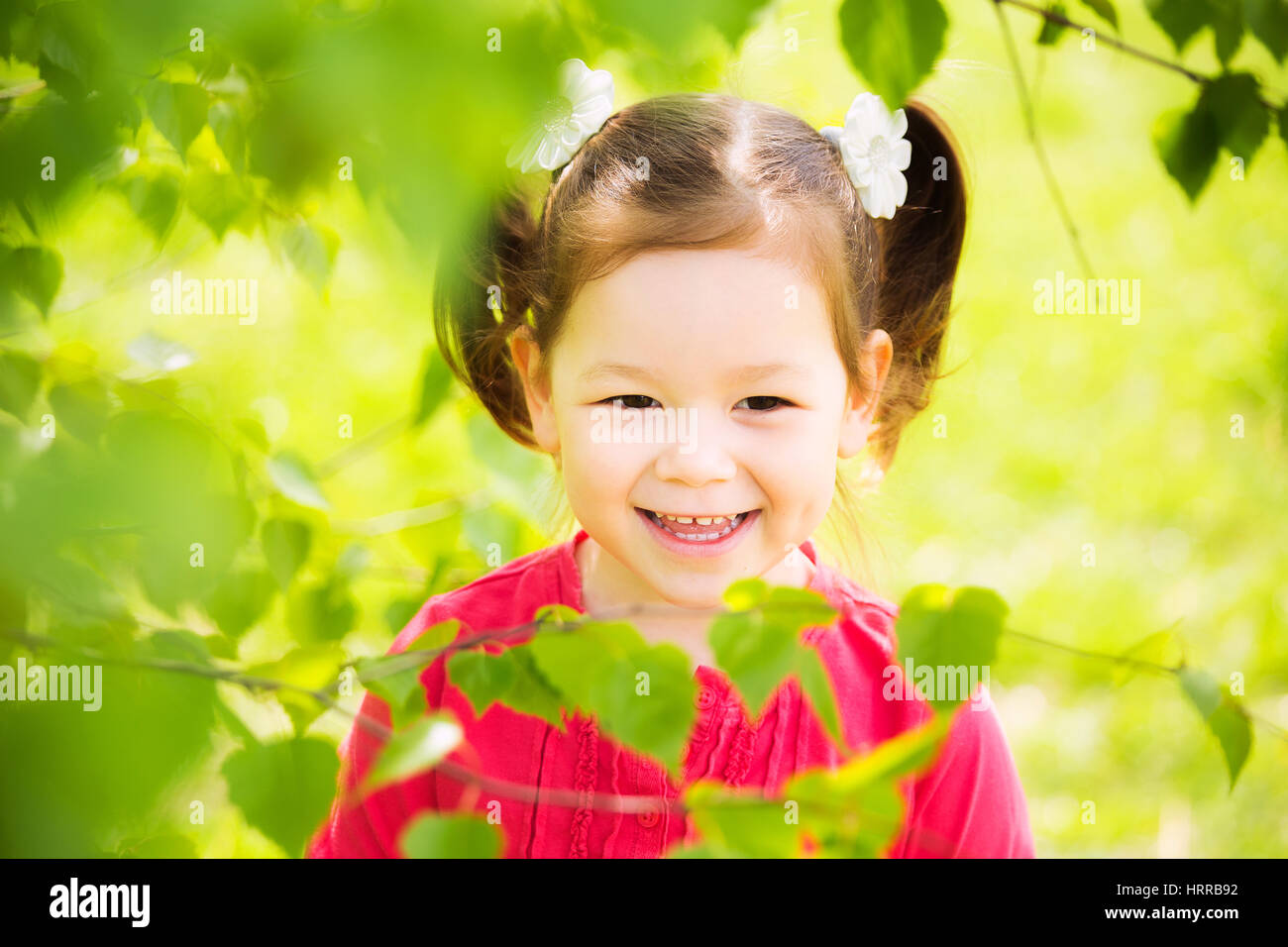 Closeup portrait of cute funny laughing girl of four years old playing cheerfully outside in spring sunny city park. - Stock Image
