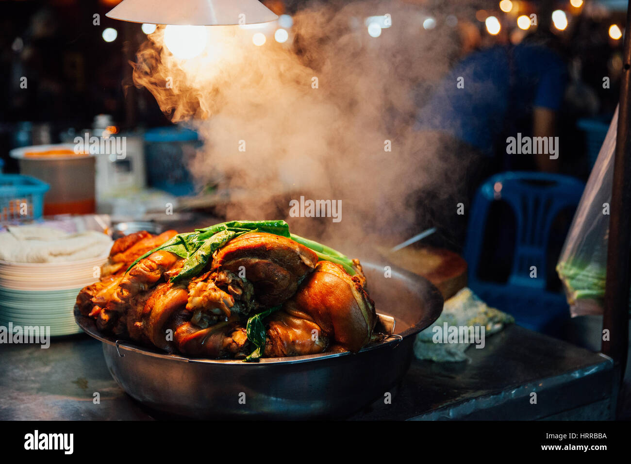 Hot pork cools down at the Saturday Night Market stall in Chiang Mai, Thailand. - Stock Image