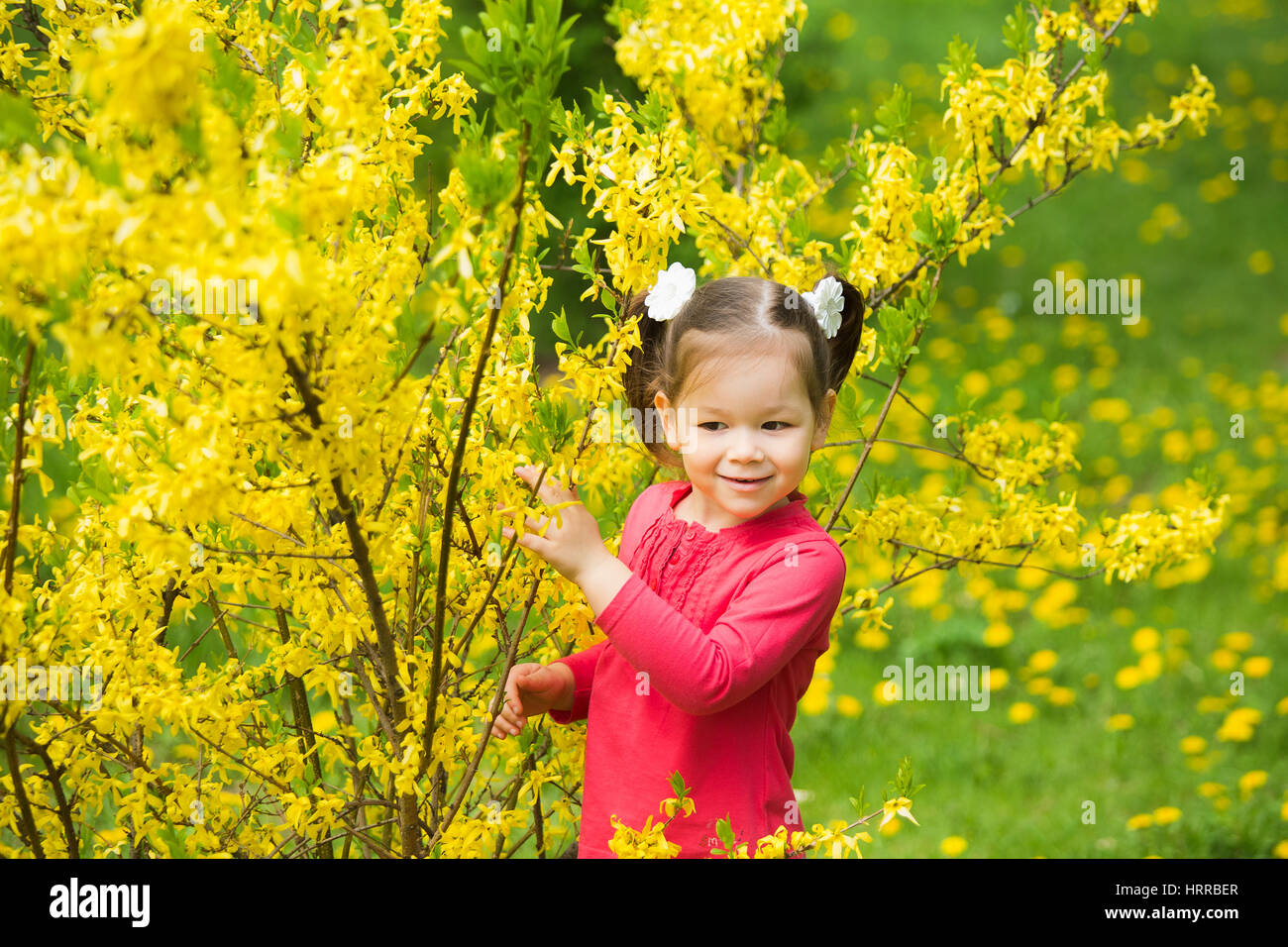 Cute funny girl of four years old playing cheerfully outside in spring sunny city park. Horizontal color photography. - Stock Image