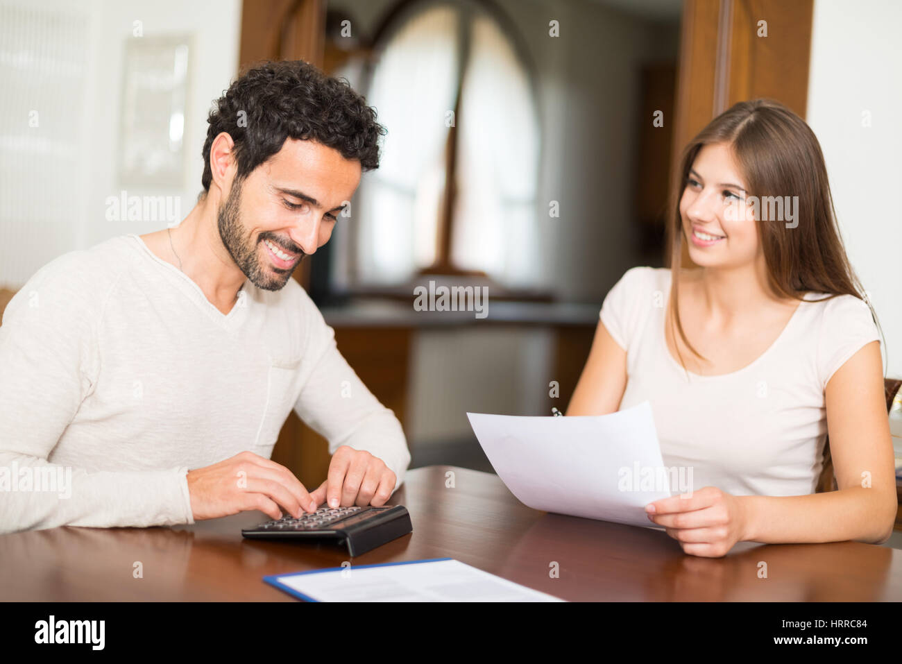 Happy couple calculating their expenses together - Stock Image