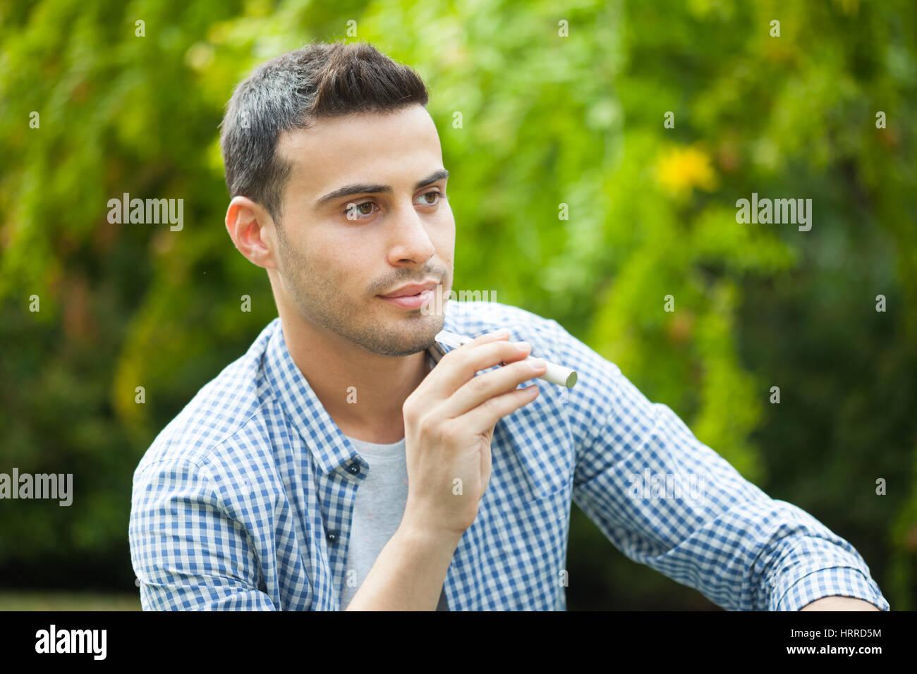 Man smoking an electronic cigarette outdoor - Stock Image