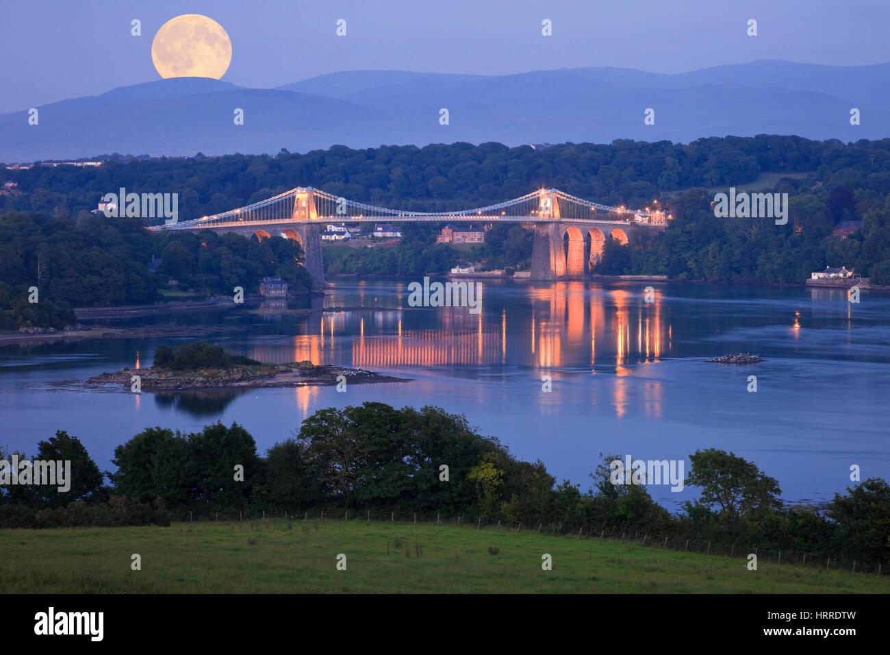 Moonrise full moon rising over Menai Strait coast with Menai suspension bridge illuminated at night. Menai Bridge, - Stock Image