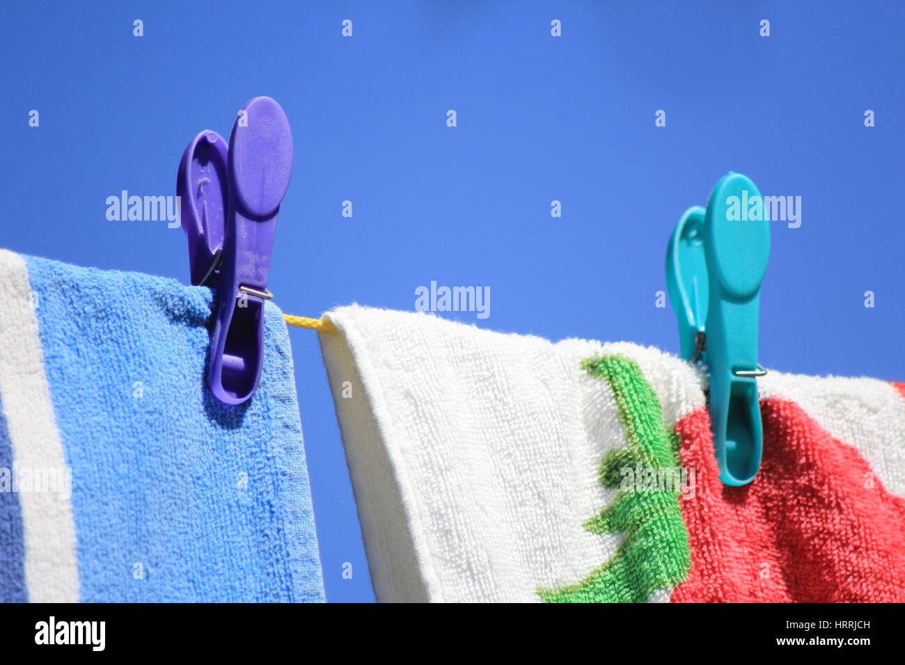Bright colored towels pegged to a washing line against a clear blue sky - Stock Image