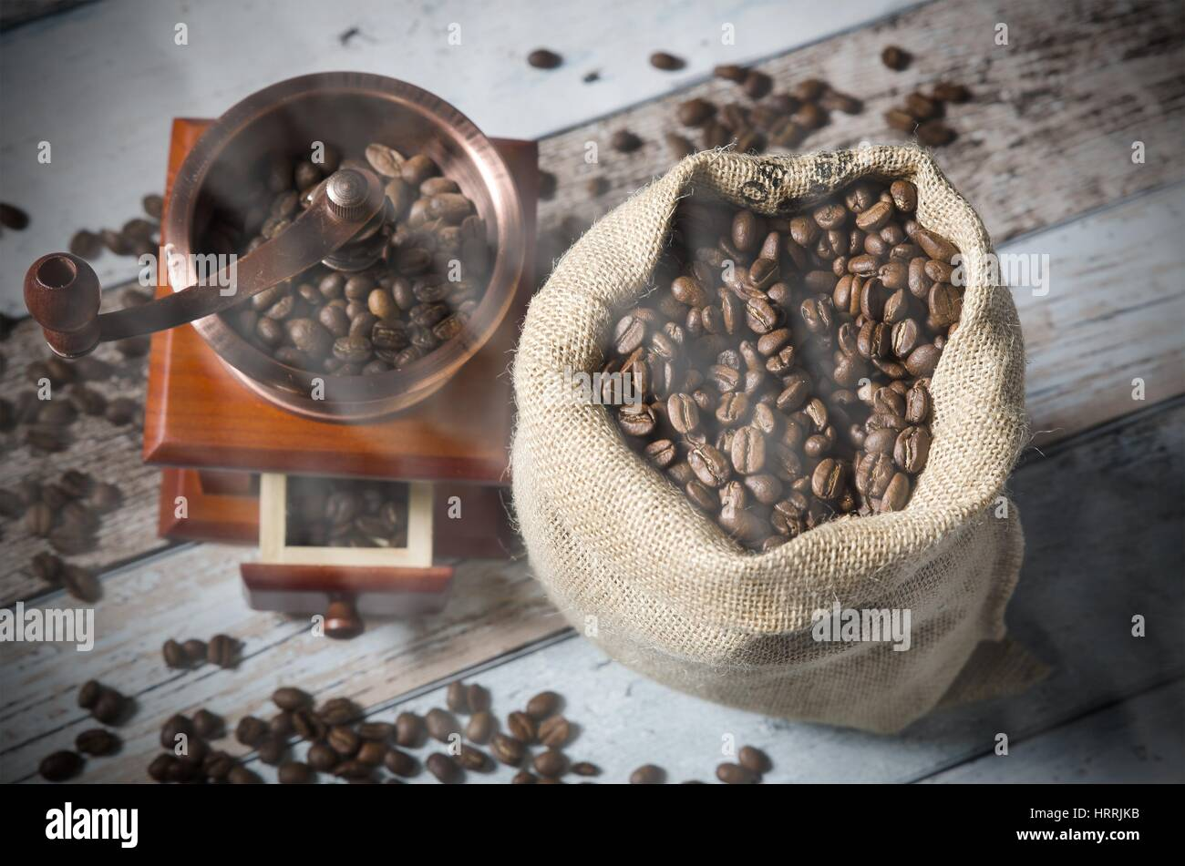Coffee grinder with roasted beans. Vintage mill composition on wooden background Stock Photo
