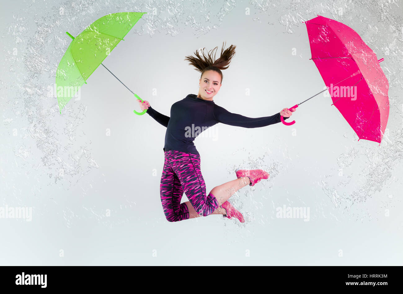Woman in jump with an umbrella. Frozen motion. - Stock Image