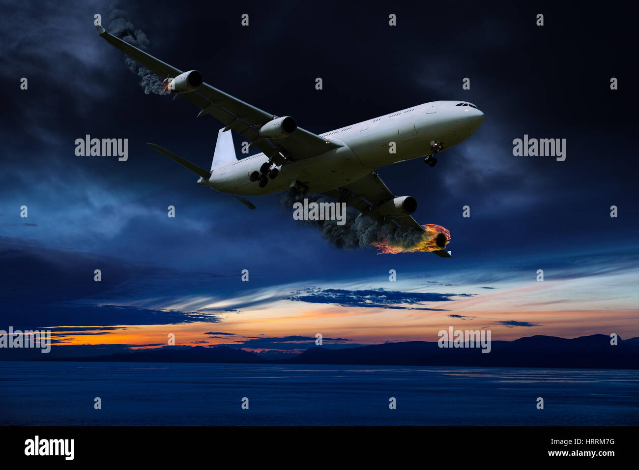 Cinematic portrayal of a fictitious plane in distress flying over the ocean at sunrise with its engines on fire. - Stock Image