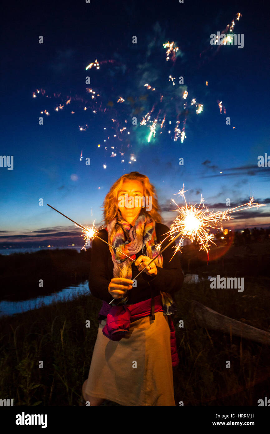 A woman holding sparklers at dusk celebrating the 4th of July at Birch Bay, Washington, USA. - Stock Image