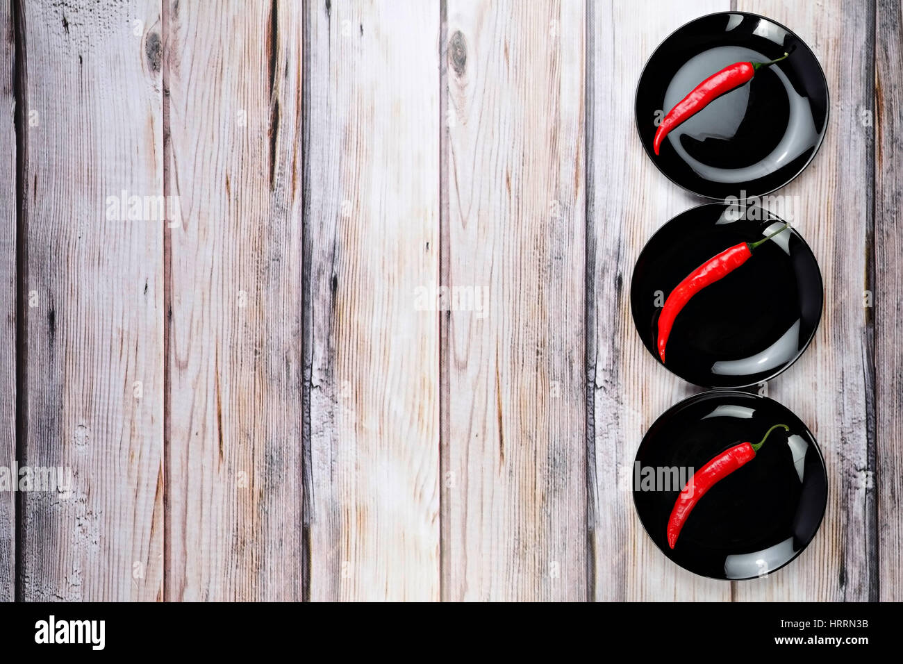Red pepper on black dish. Black plates on wooden table. Bright food background. Free space for text on wooden background. - Stock Image
