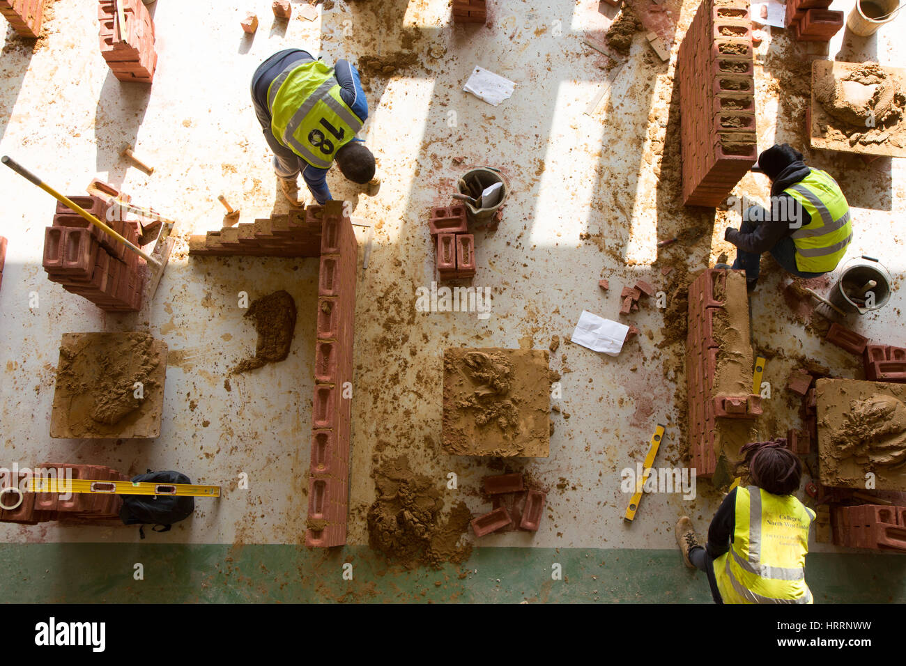 Apprentice builders learn how to construct a wall using bricks and mortar - Stock Image