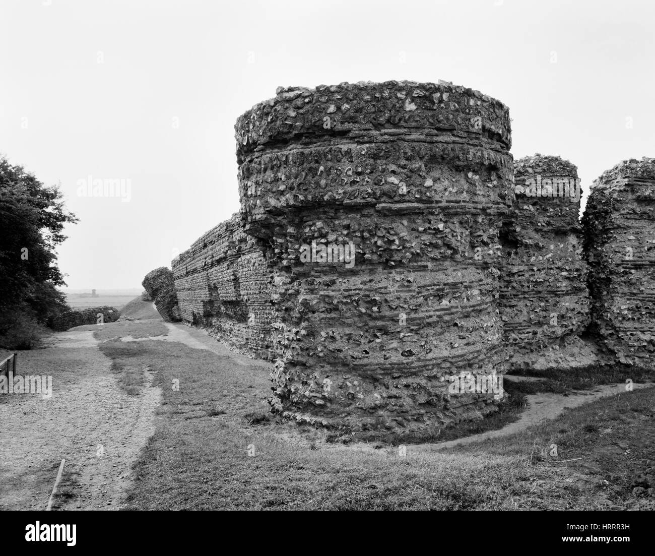 Looking NW at the S wall (L) & SE projecting bastion of Burgh Castle Roman fort, Norfolk, built in the C3rdAD - Stock Image