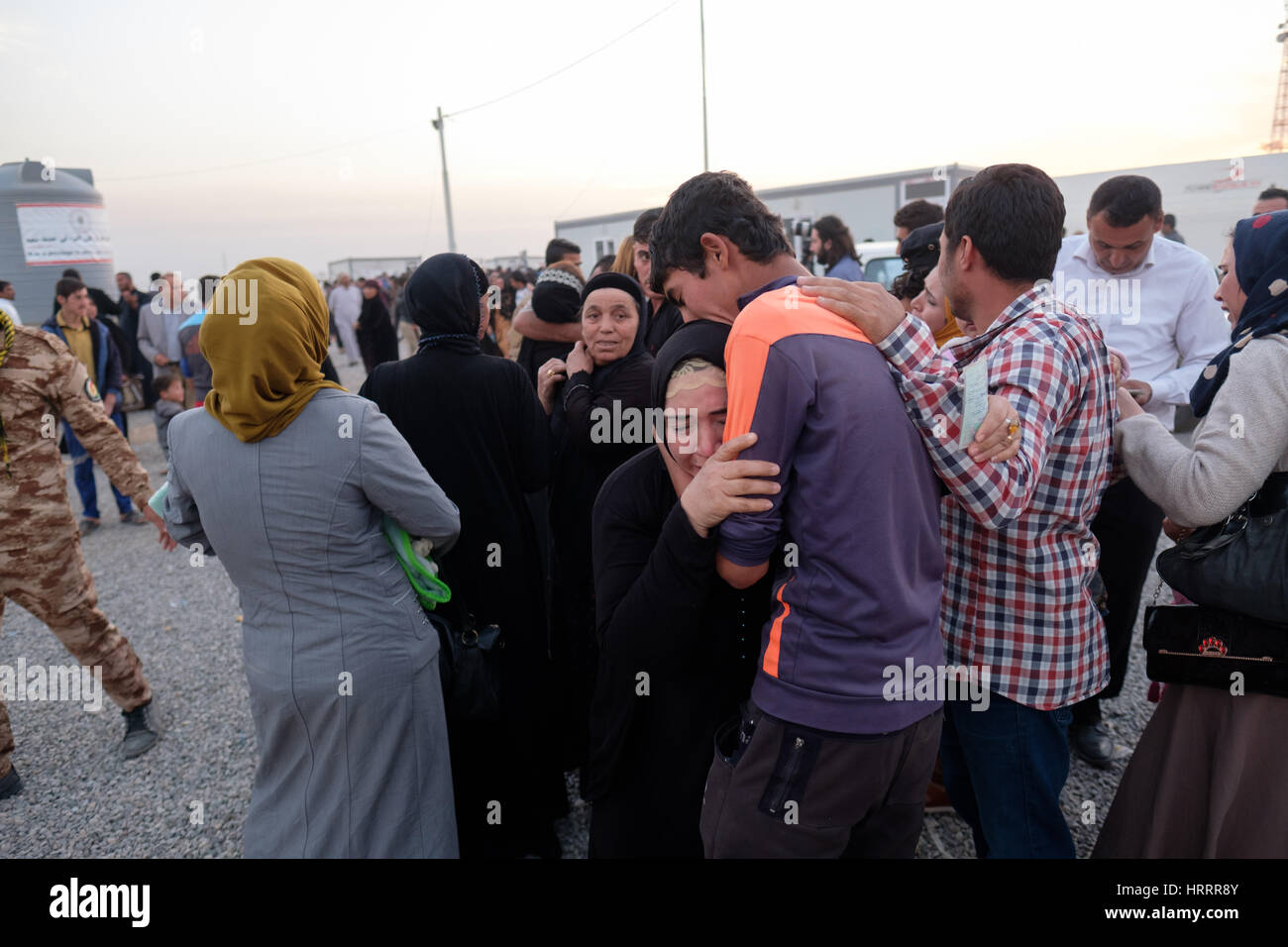 refugees fleeing fighting in Mosul have emotional reunion with family members who they have not seen since bieng - Stock Image