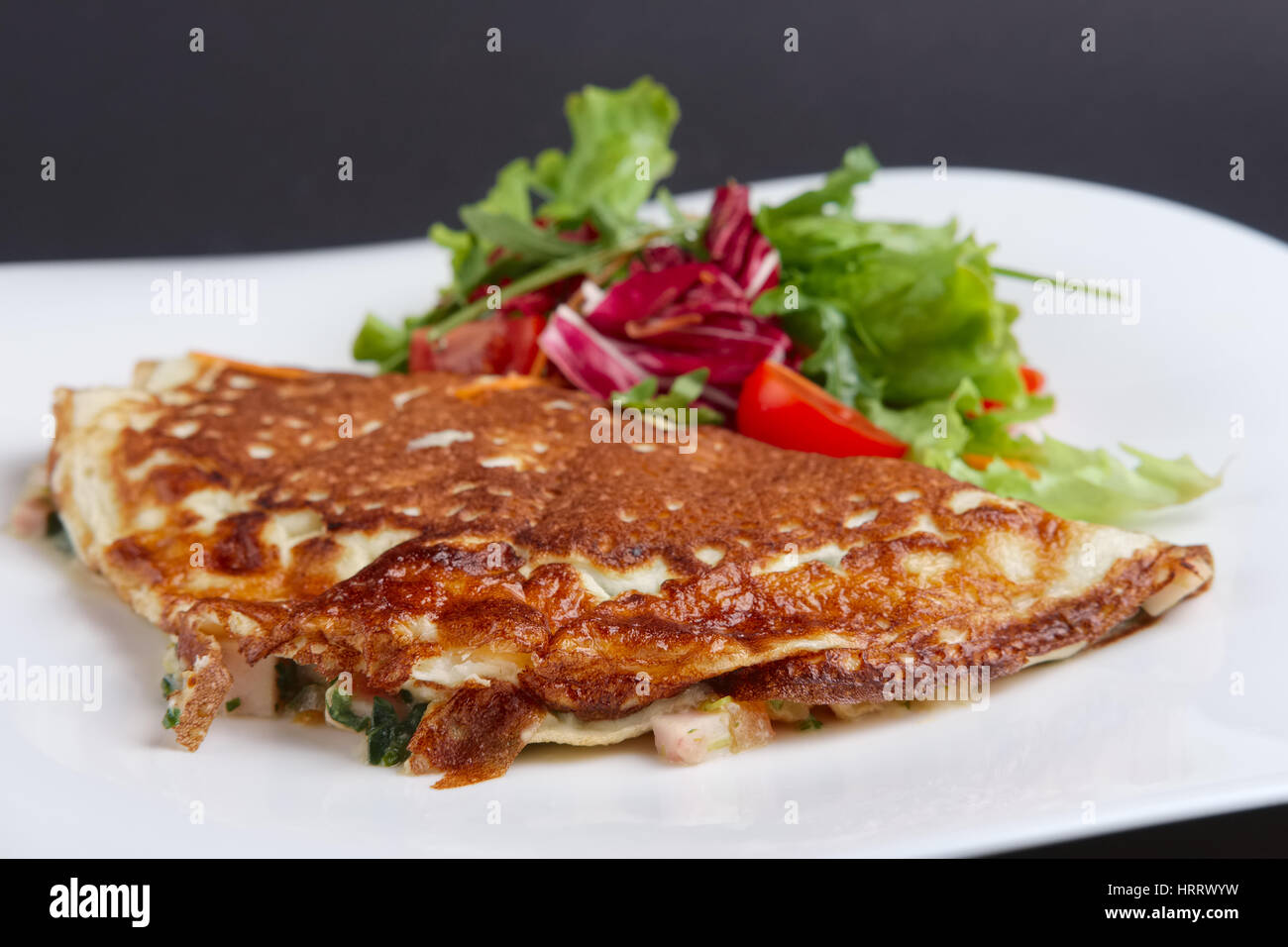 Closeup of omelet with ham and vegetables - Stock Image