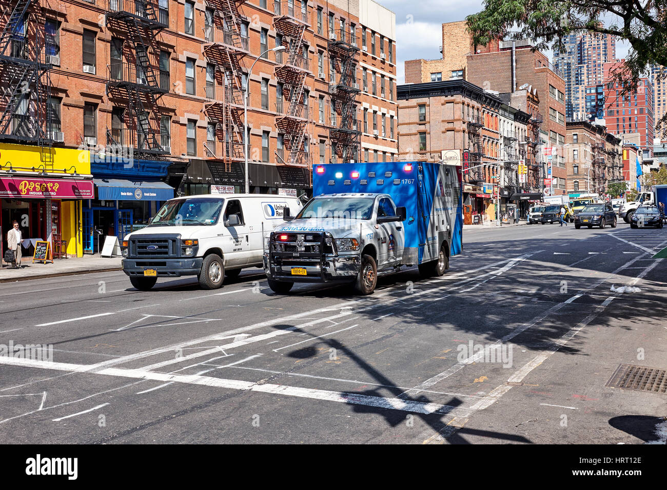 NEW YORK CITY - SEPTEMBER 26, 2016: Ambulance with emergency light and a small truck on 9th Avenue and 51st W Street Stock Photo