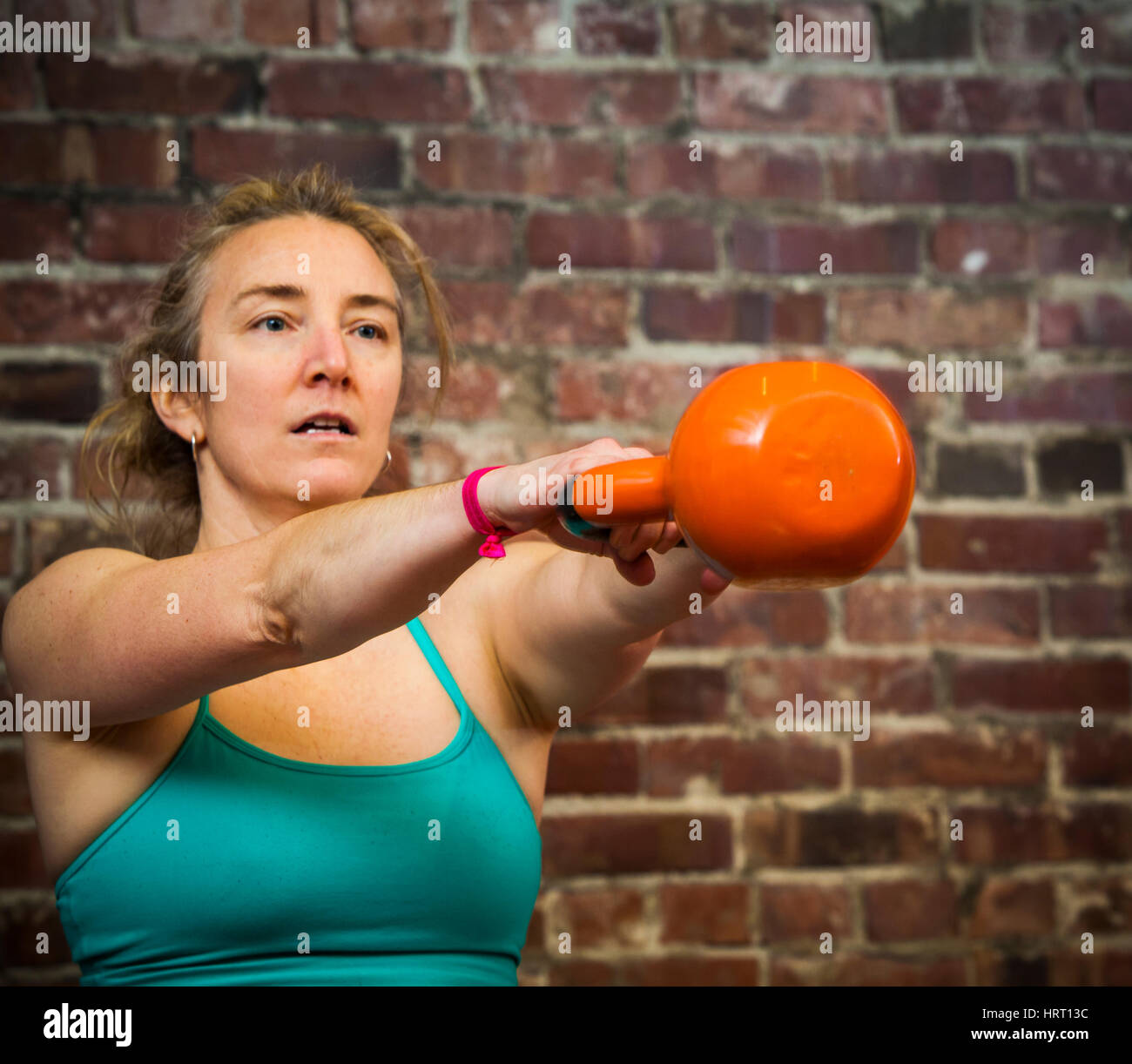 A woman in her early 40's swinging a kettlebell while working out.