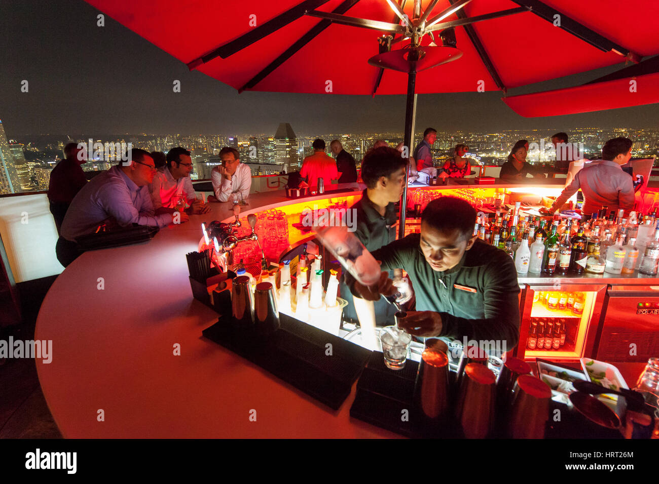 Roof top bar, CÉ LA VI SkyBar, bar, bartender, red sunshades, on the Marina Bay Sands, Singapore, Asia, Singapore - Stock Image