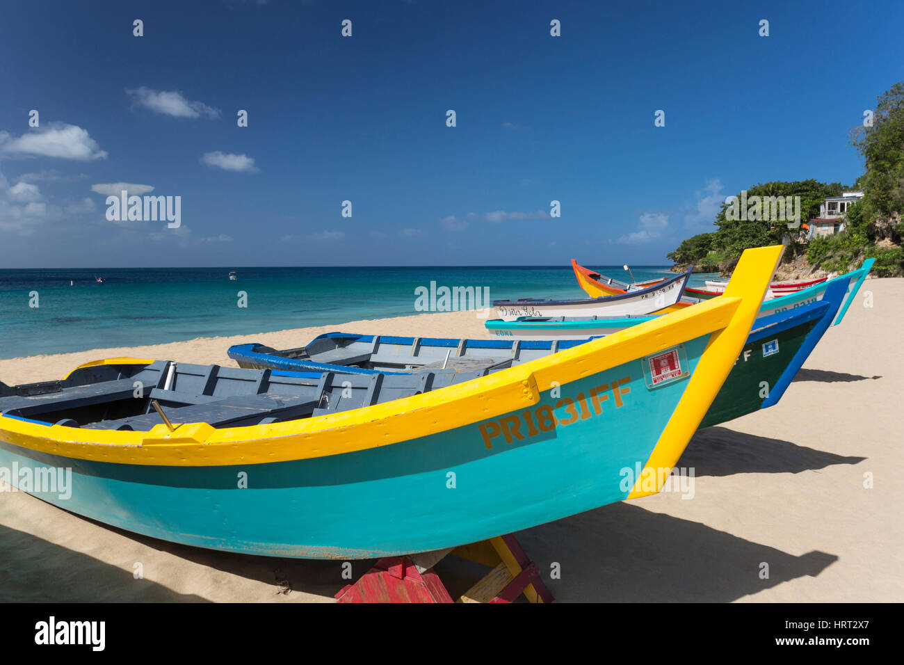 ROW OF BRIGHTLY PAINTED YOLA FISHING BOATS CRASH BOAT BEACH AGUADILLA PUERTO RICO - Stock Image