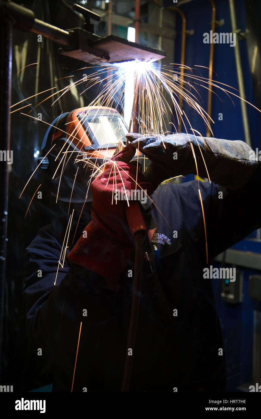 A welder at work using a protective mask - Stock Image