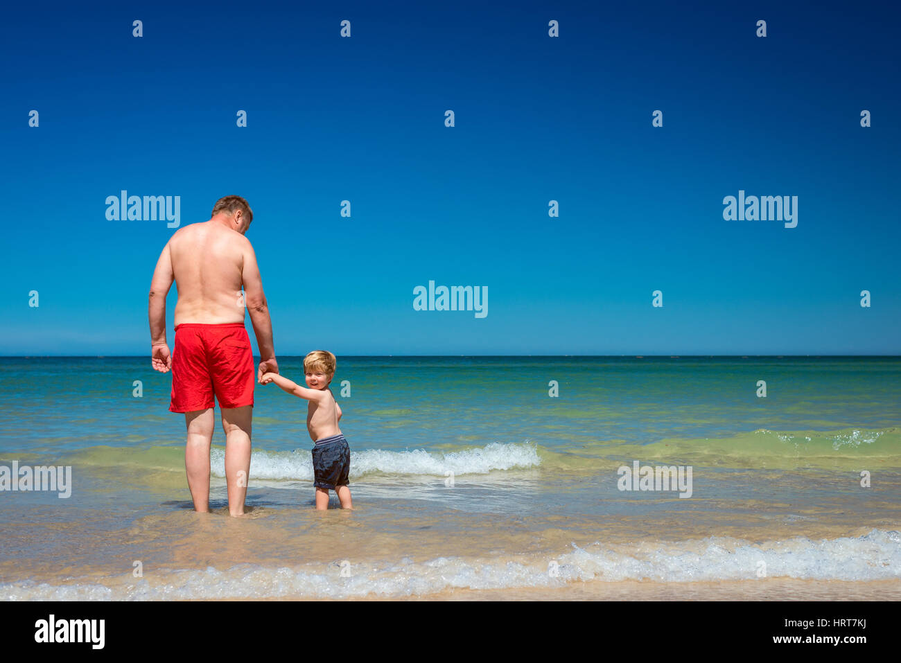 Grandfather with grandson holding hands on beach - Stock Image