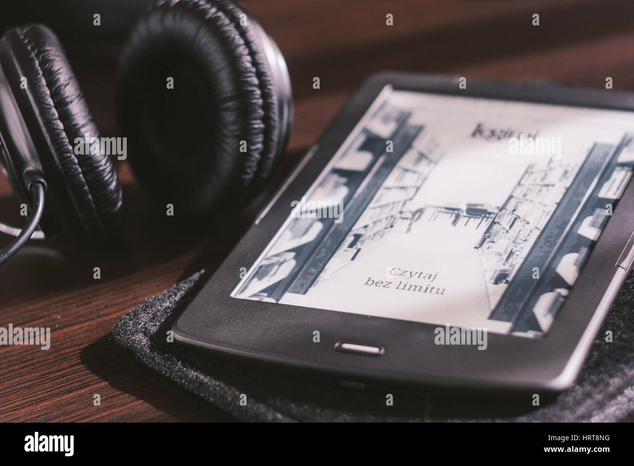 Pair of headphones and open ebook reader on the desk - Stock Image