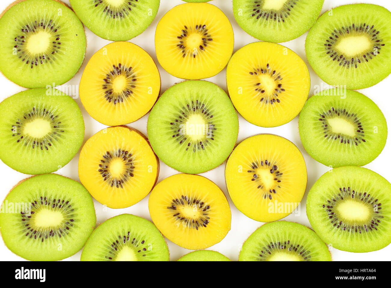 slices of fresh green and yellow kiwi fruits as a food background texture Stock Photo