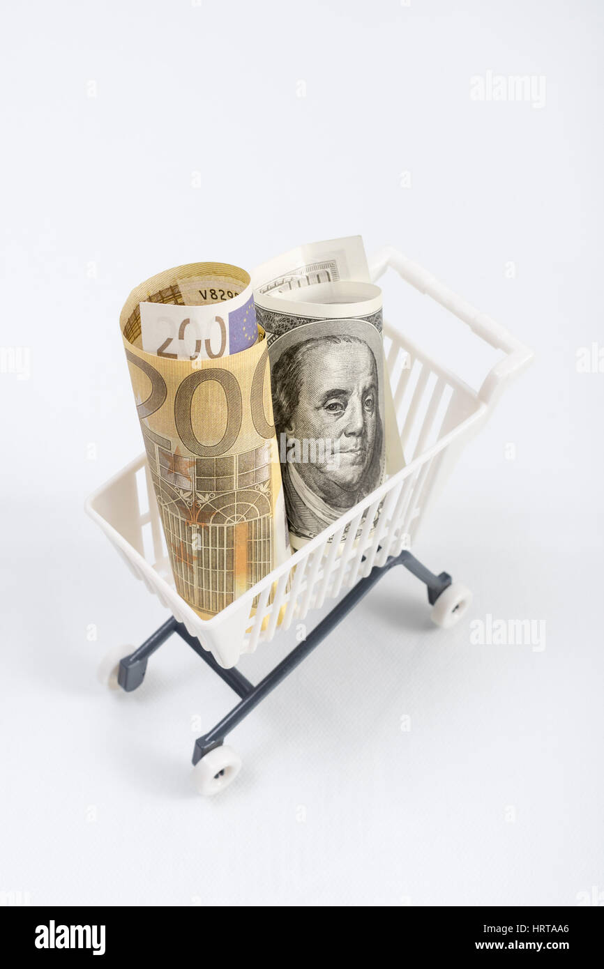 US100 Dollar and 200 Euro banknotes in shopping cart / trolley. Metaphor for exchange rates, free trade, trade war, - Stock Image