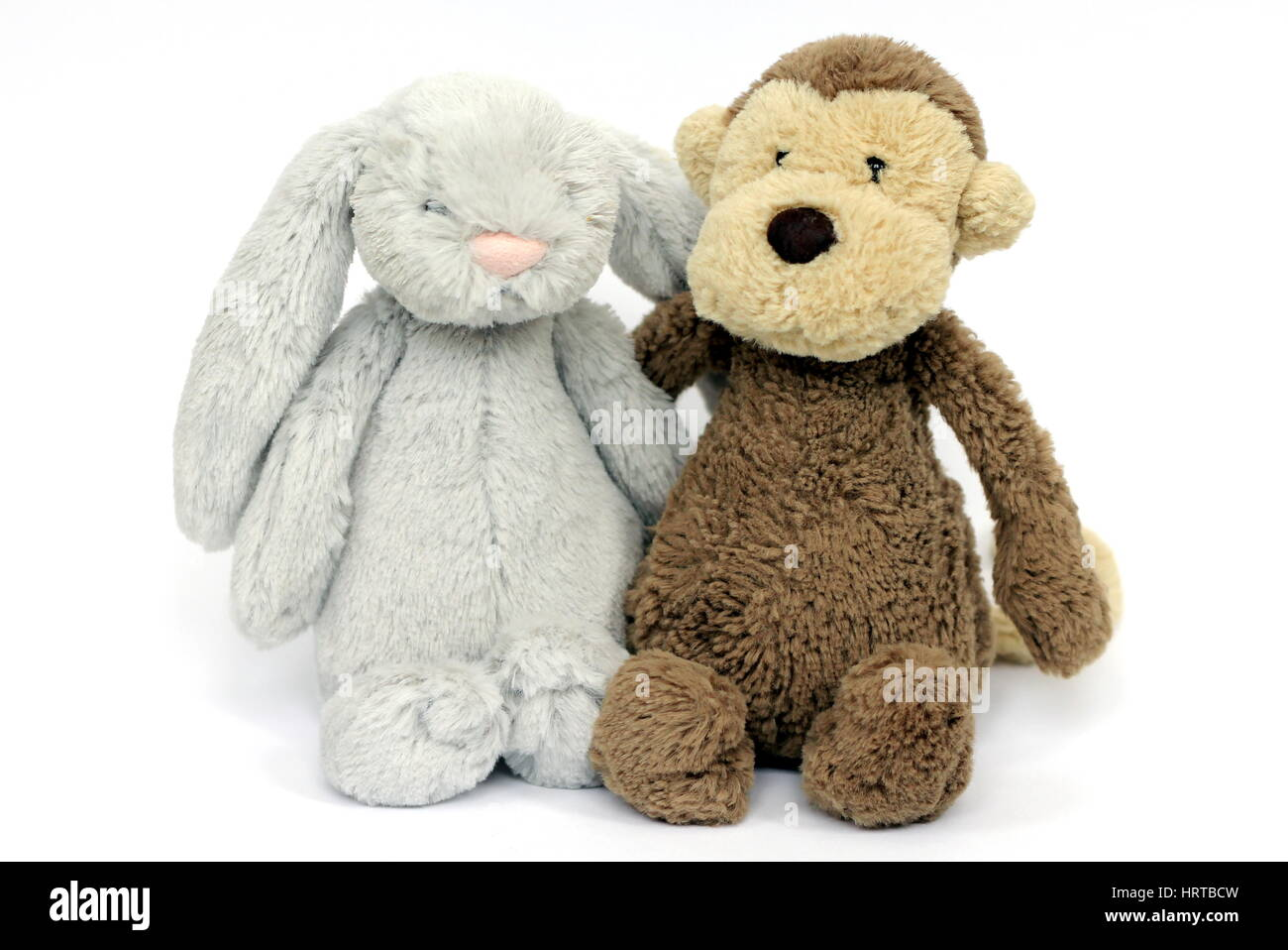 Brown fluffy monkey and grey fluffy rabbit soft toy - Stock Image