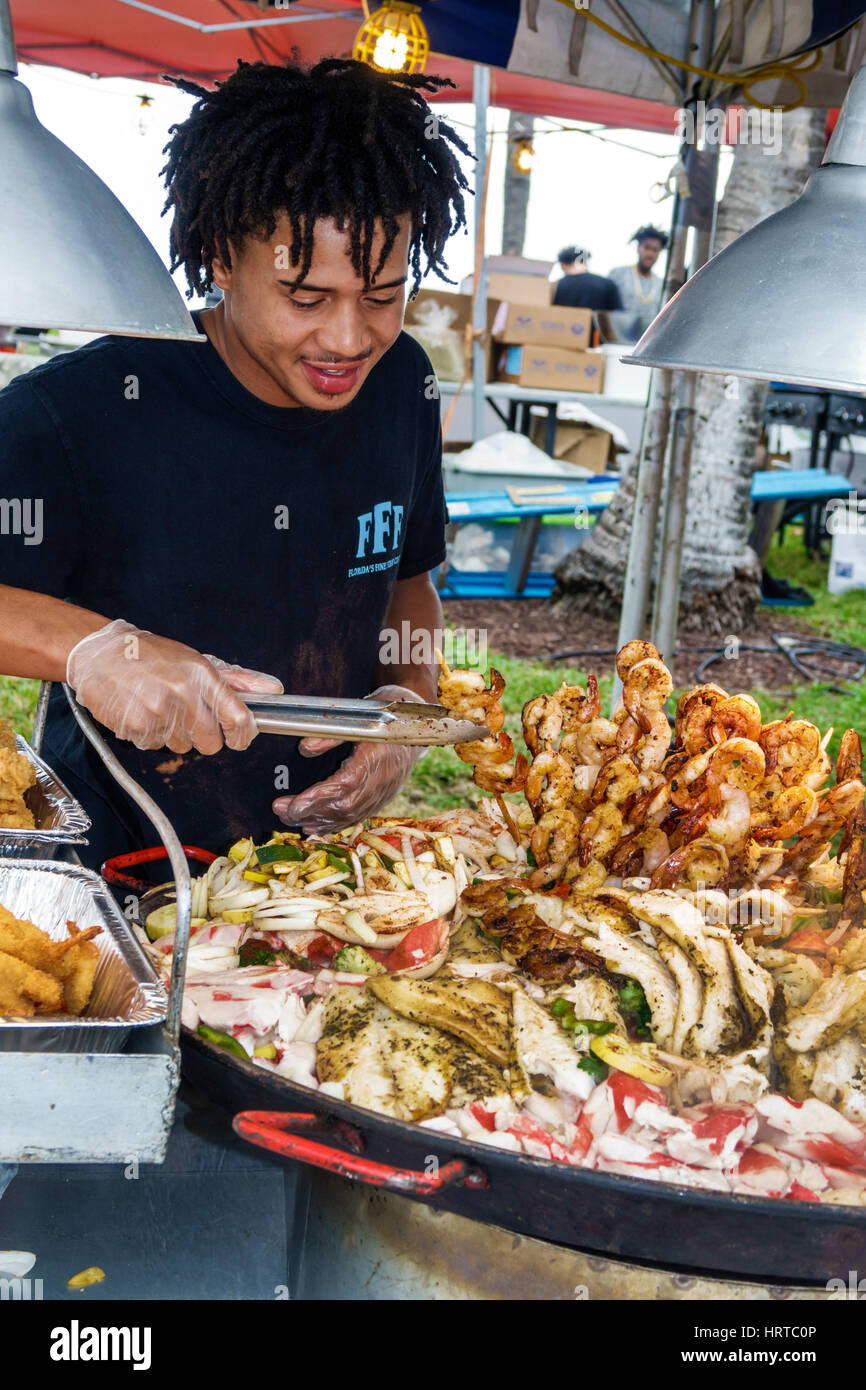 Miami Beach Florida Art Deco Weekend community festival vendor street food seafood shrimp skewers crabs Black man - Stock Image
