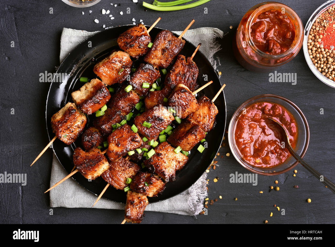 Barbecued pork kebabs and tomato sauce, top view - Stock Image