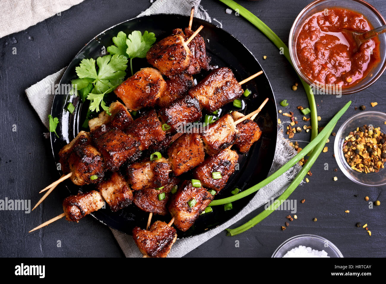 Bbq meat on wooden skewers on plate, top view - Stock Image