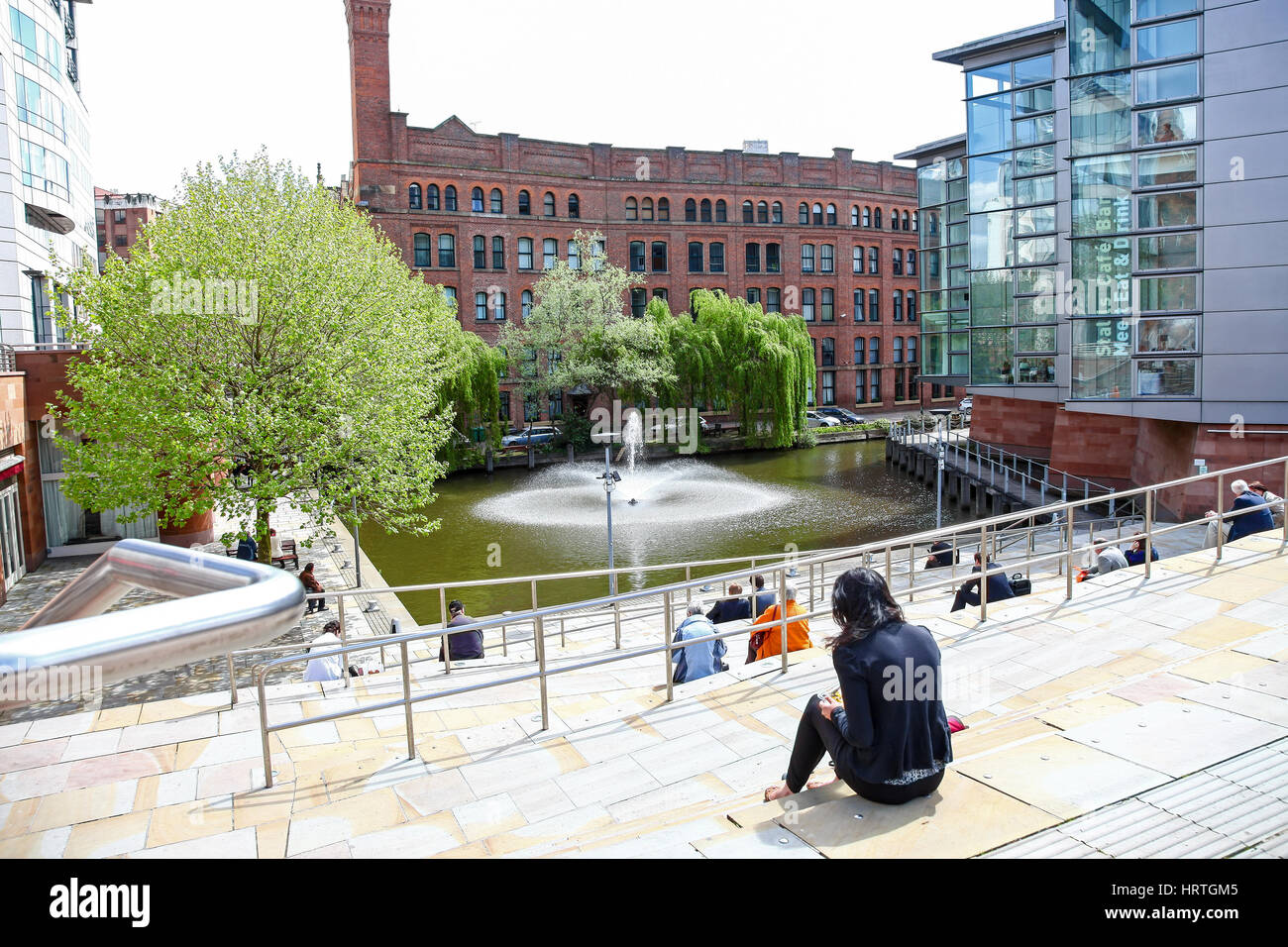 People sitting outside on the steps at Barbirolli Square, Manchester City centre, England UK - Stock Image