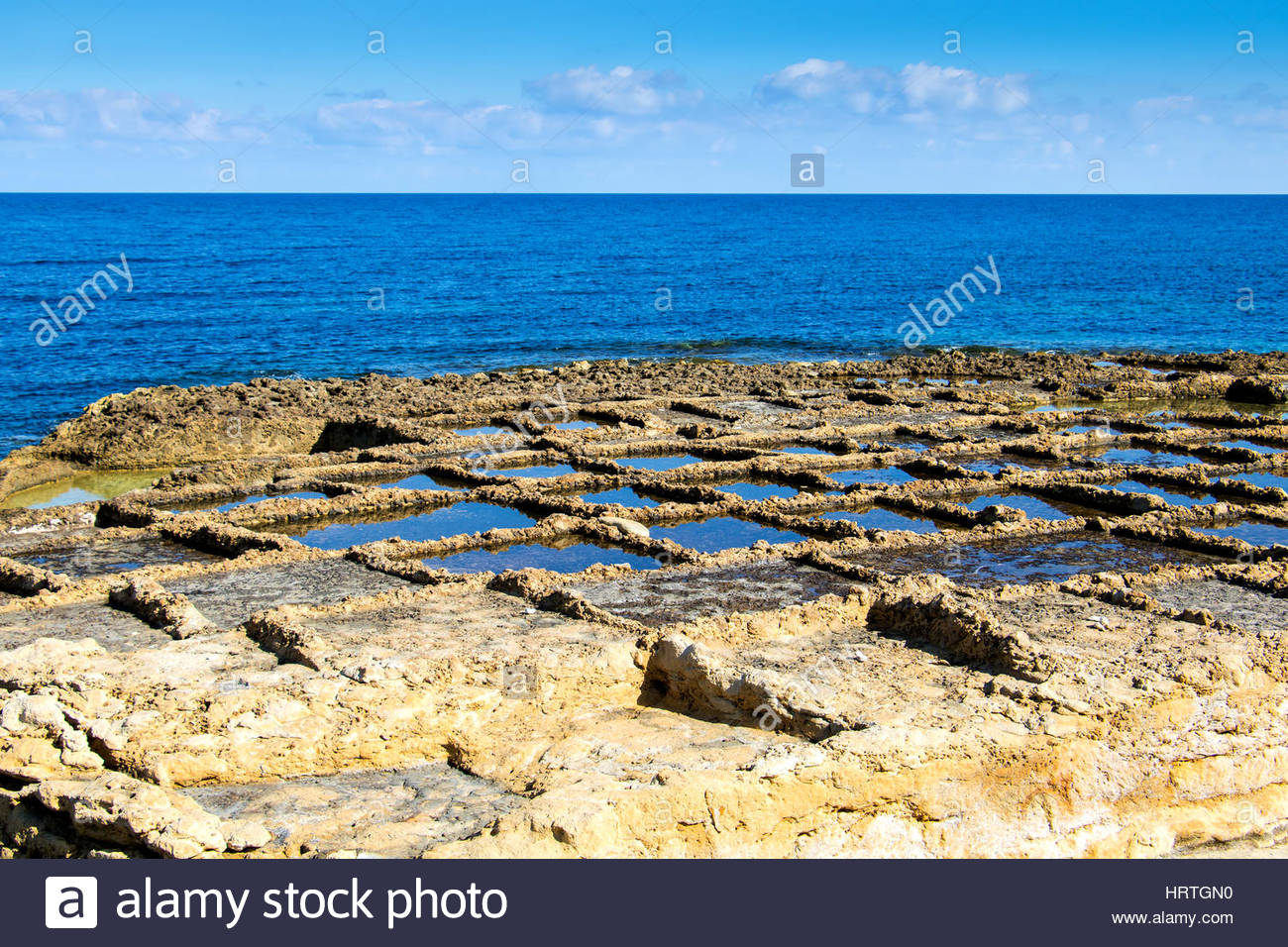 Abandoned historical Salina salt pans, salines, build into the rocky cliffs of the mediterranean sea coast of Gozo - Stock Image