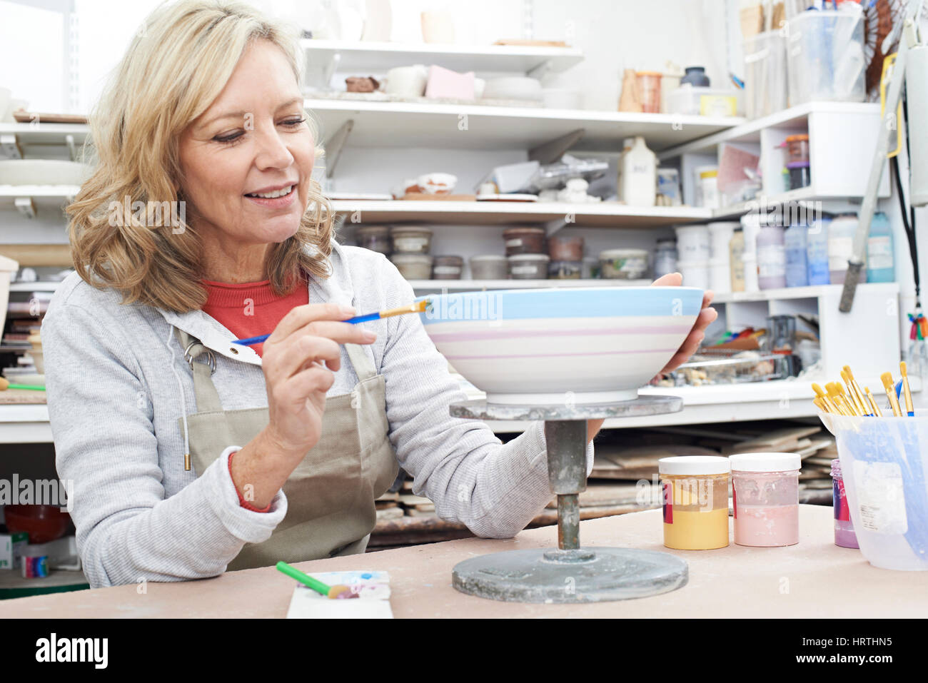 Mature Woman Decorating Bowl In Pottery Class - Stock Image