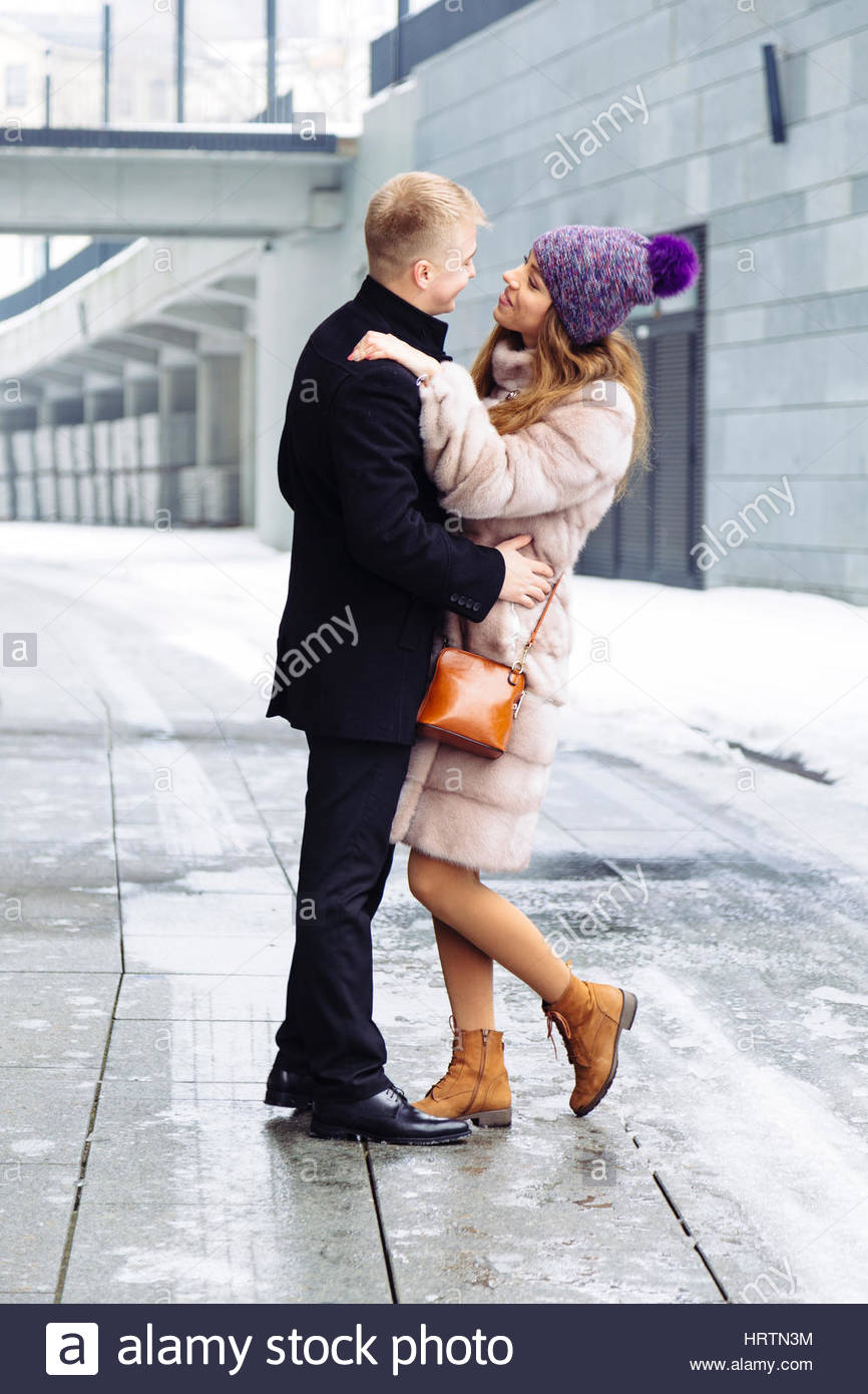 Happy woman and man couple walking together in the city holding hands together. Relationship concept. Woman wearing Stock Photo
