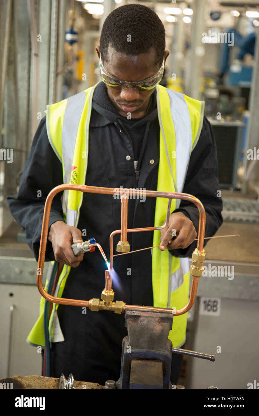 A young man learning welding skills at college - Stock Image