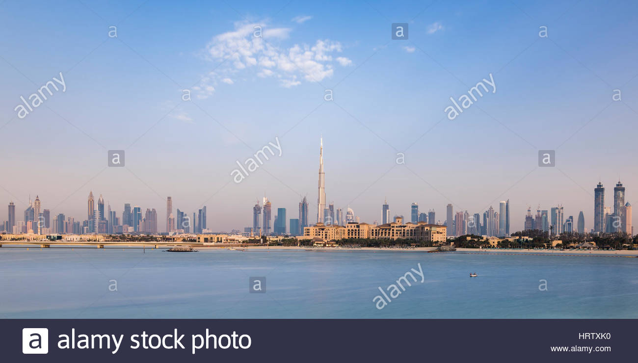 Skyline of Dubai with the Four Season Hotel (the large brown building with access to the beach) and the iconic Burj - Stock Image