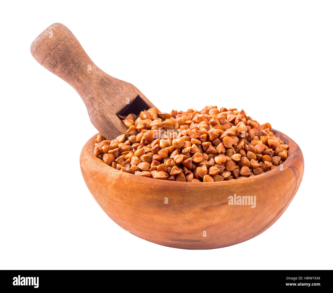 Wooden bowl of uncooked buckwheat groats with scoop. Isolated with clipping path - Stock Image